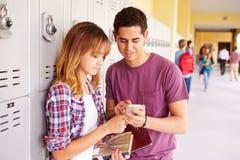 Estudiantes de la High School secundaria por los armarios que miran el teléfono móvil Foto de archivo libre de regalías