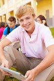 Estudiantes de la High School secundaria que estudian al aire libre en campus Imagenes de archivo