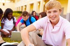 Estudiantes de la High School secundaria que estudian al aire libre en campus Foto de archivo libre de regalías