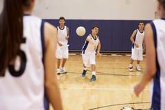 Estudiantes de la High School secundaria que juegan la bola de Dodge en gimnasio Imagenes de archivo