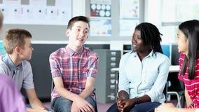 Estudiantes de la High School secundaria que tienen discusión informal con el profesor de sexo femenino en sala de clase almacen de metraje de vídeo