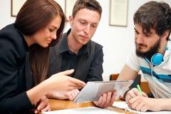 Estudiantes de la High School secundaria que usan el ordenador de la tableta Fotografía de archivo