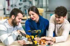 Estudiantes de la robótica que preparan el robot para probar en worksh Foto de archivo