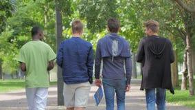 Estudiantes de la universidad que caminan junto en campus almacen de metraje de vídeo