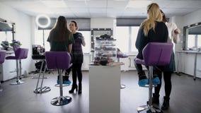 Estudiantes de la universidad que intentan hacer su primer maquillaje en el entrenamiento práctico en salón de belleza profesiona almacen de metraje de vídeo