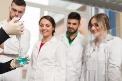 Estudiantes de los científicos con el profesor In Lab Classrom Foto de archivo