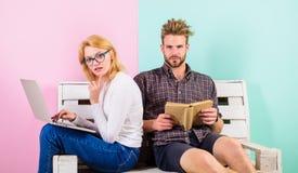 Estudiantes de los pares con estudiar del libro y del ordenador portátil Los estudiantes modernos utilizan acercamiento digital a fotos de archivo