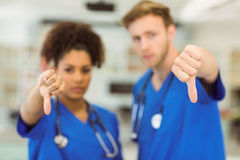 Estudiantes de medicina jovenes que muestran los pulgares abajo fotografía de archivo