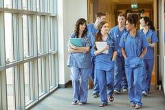 Estudiantes de medicina que caminan a través del pasillo Imagen de archivo