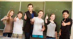 Estudiantes de motivación del profesor en clase de escuela foto de archivo