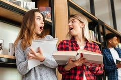 Estudiantes de mujeres chocados jóvenes que se colocan en biblioteca Imagenes de archivo