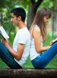 Estudiantes de nuevo a la lectura trasera un libro al aire libre Fotografía de archivo