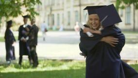 Estudiantes de tercer ciclo en el equipo académico que abraza y que hace girar, amistad de la universidad almacen de metraje de vídeo