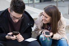 Estudiantes del collage de la muchacha y del muchacho con los teléfonos elegantes en el campus Foto de archivo libre de regalías