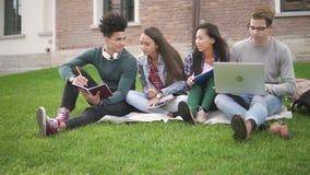 Estudiantes del grupo cuatro que hacen el nuevo trabajo, el hablar, sentándose en fondo del campus almacen de video