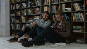 Estudiantes del inconformista que estudian en biblioteca en la universidad almacen de metraje de vídeo