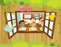 Estudiantes dentro de la sala de clase con los pájaros en la ventana Fotos de archivo libres de regalías