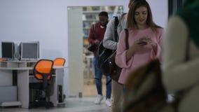Estudiantes diversos que hojean los teléfonos móviles después de conferencia almacen de video