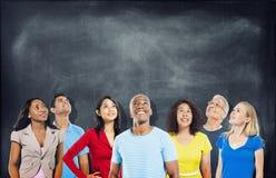 Estudiantes diversos que miran para arriba con la pizarra Fotografía de archivo