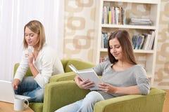 Estudiantes - dos adolescentes con la computadora portátil y el libro Foto de archivo