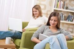 Estudiantes - dos adolescentes con la computadora portátil y el libro Imágenes de archivo libres de regalías