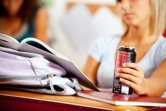 Estudiantes: El foco encendido puede de soda en la mano del estudiante Fotografía de archivo libre de regalías