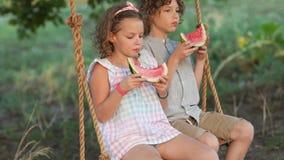estudiantes el vacaciones Los niños comen la sandía que se sienta en un oscilación La muchacha escupe las semillas almacen de metraje de vídeo