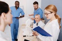 Estudiantes elegantes que aprueban el examen en la universidad médica fotos de archivo libres de regalías