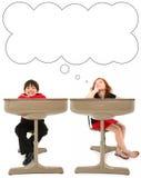 Estudiantes elementales en escritorio Imágenes de archivo libres de regalías