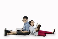 Estudiantes elementales que se sientan en el estudio Fotografía de archivo