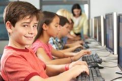 Estudiantes elementales que trabajan en los ordenadores en sala de clase imagen de archivo