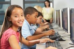 Estudiantes elementales que trabajan en los ordenadores en sala de clase