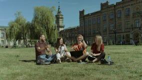 Estudiantes emocionados que comprueban el examen aprobado en el ordenador portátil almacen de video