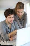 Estudiantes en casa que trabajan en el ordenador portátil Foto de archivo libre de regalías