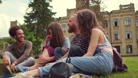 Estudiantes en el campus que se sienta en hierba, hablar y la risa almacen de metraje de vídeo