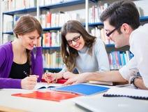 Estudiantes en el trabajo en una biblioteca Fotos de archivo libres de regalías