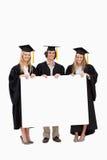 Estudiantes en el traje graduado que lleva a cabo una muestra en blanco Fotos de archivo