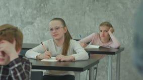 Estudiantes en el uniforme escolar que toma el examen en el escritorio en una sala de clase almacen de metraje de vídeo
