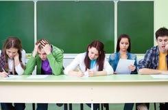Estudiantes en examen en clase Fotos de archivo