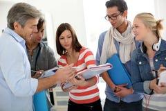 Estudiantes en la escuela que hablan con el profesor Imágenes de archivo libres de regalías