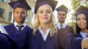 Estudiantes en la regalía académica que toma el selfie el día de graduación, logro fotos de archivo libres de regalías
