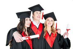 Estudiantes en los casquillos académicos que se colocan de abarcamiento con los diplomas Fotografía de archivo libre de regalías