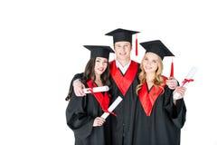 Estudiantes en los casquillos académicos que se colocan de abarcamiento con los diplomas y de mirada de la cámara Fotografía de archivo libre de regalías