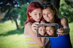 estudiantes en parque con PC de la tableta Imagen de archivo libre de regalías