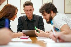 Estudiantes en sala de clase con la tableta electrónica Fotos de archivo