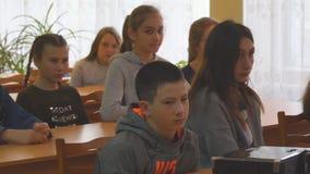 Estudiantes en sus escritorios en la sala de clase almacen de metraje de vídeo