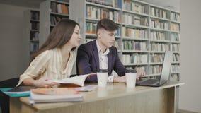 Estudiantes en una biblioteca en el ordenador y libro del uso de la escuela y charla para los proyectos almacen de video