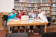 Estudiantes en una biblioteca que muestra los pulgares para arriba Fotos de archivo libres de regalías
