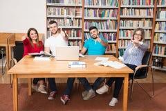 Estudiantes en una biblioteca que muestra los pulgares para arriba Foto de archivo libre de regalías