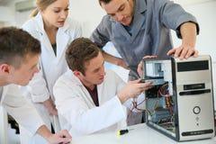Estudiantes en una clase con el profesor que repara el hardware Imágenes de archivo libres de regalías